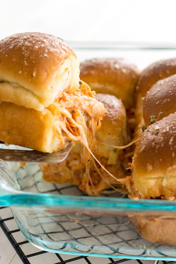 Spatula serving of Slow Cooker Chicken Parmesan Sliders with melted cheese