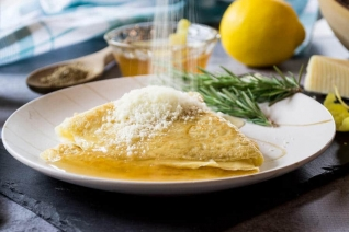 Verter huevos en una sartén de desayuno de salchichas y calabacín