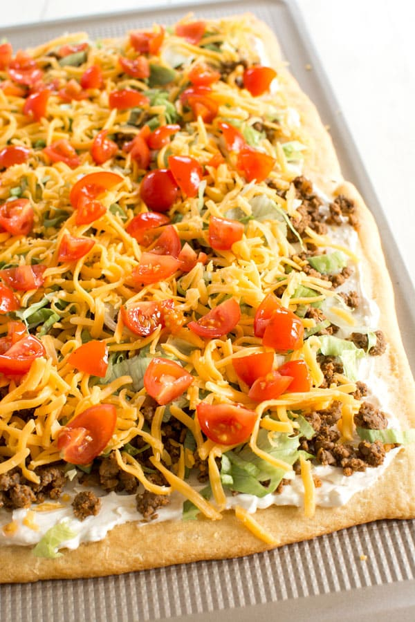 Taco Pizza Appetizer with a crescent roll crust. Easy cream cheese sauce is so zesty!