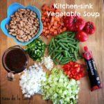 Verduras cortadas en cubitos para hacer una sopa de verduras en el fregadero de la cocina: zanahorias cortadas en cubitos, judías verdes, pimientos verdes, apio, cebollas, ajo, pimiento rojo, judías blancas, pasta de tomate, caldo de verduras