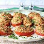 Placa de los tomates de ciruelo asados ??italianos con las migajas de pan y el queso.