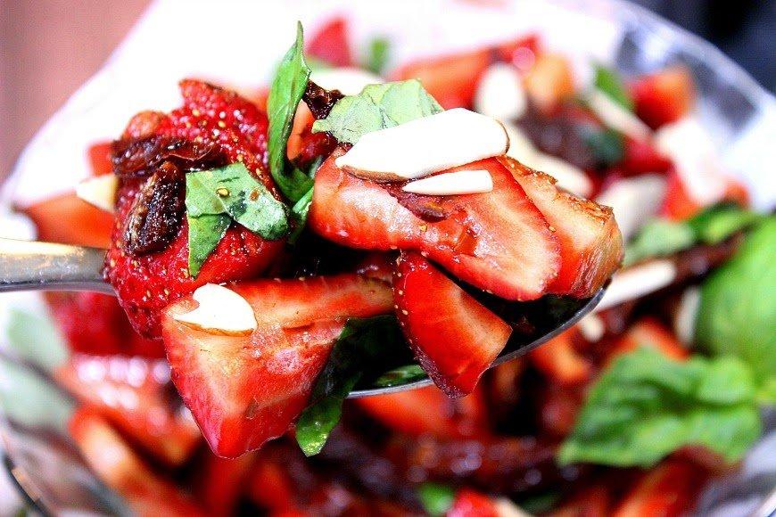 Receta de fresas, tomates secados al sol y ensalada de albahaca. Dulces fresas y tarta de tomates secos se mezclan bien con las hojas frescas de albahaca. Luego se visten con un ligero y sabroso vinagre balsámico de vainilla y se rematan con rodajas de almendra.