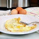 Huevos fritos en un plato blanco con un tenedor y una freidora en el fondo