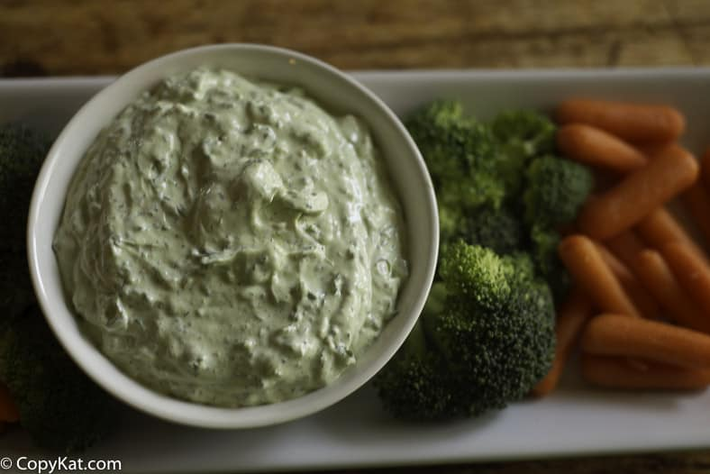 A bowl of green goddess dip and fresh vegetables