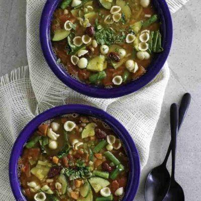 Dos tazones de sopa de minestrone casera, llena de verduras frescas y pasta