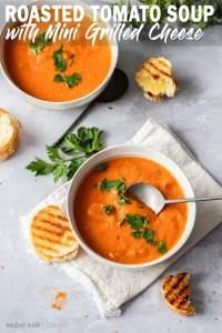 Tiro de arriba de dos tazones de sopa de tomate con perejil y sándwiches de queso a la parrilla cerca