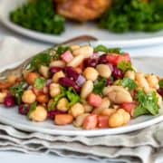 mixed bean salad on white plate with napkin