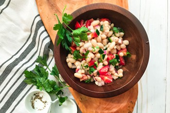 thumbsize white bean salad in wooden bowl