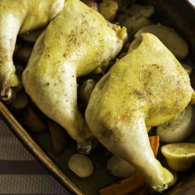 tres cuartos de pierna de pollo asado descansando sobre tubérculos