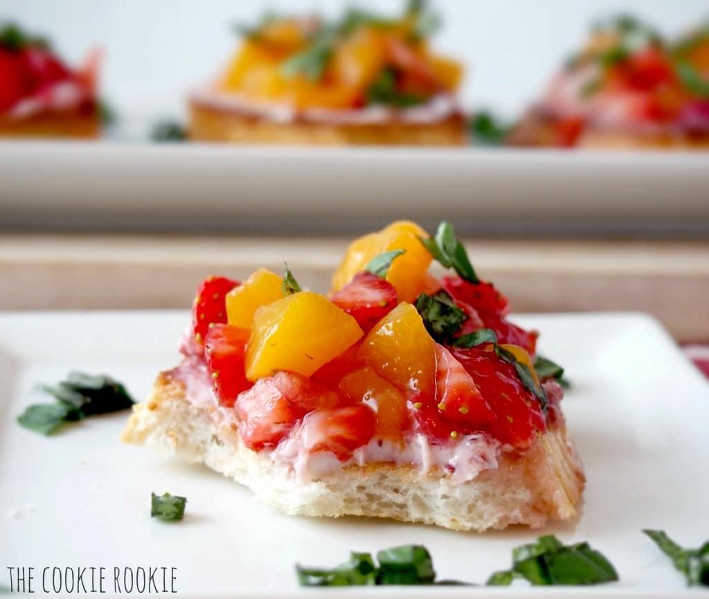 Bruschetta de frutas de verano con fresas, duraznos, albahaca, balsámico blanco de frambuesa y queso de cabra. ¡Mmm!