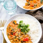 Este estofado de maní inspirado en África de olla de cocción lenta es un sabroso y sabroso curry de garbanzos y batatas, servido con arroz basmati y cubierto con cilantro. ¡También es sin gluten y vegano!