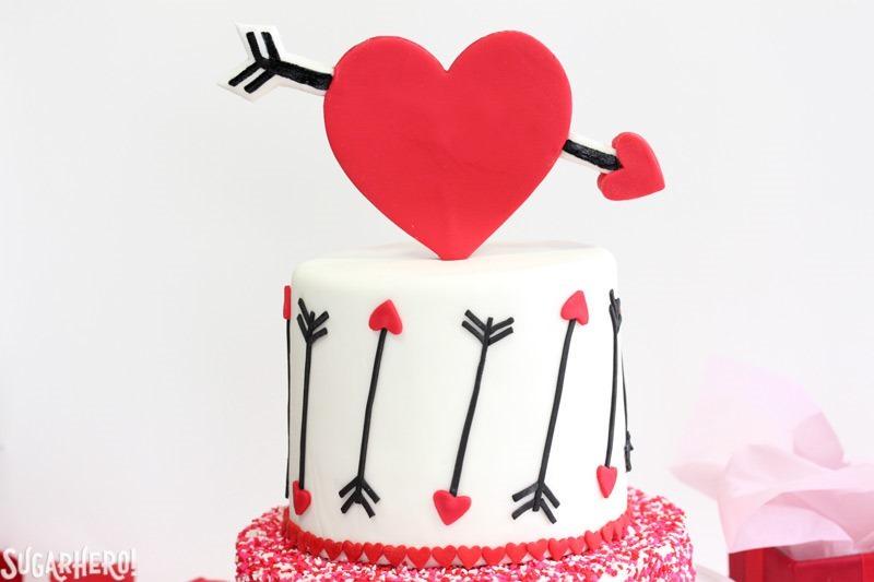 Pastel de San Valentín de terciopelo rosa y rojo: ¡un pastel de terciopelo rosa y rojo con un diseño de corazón y flecha para el Día de San Valentín! El | De SugarHero.com