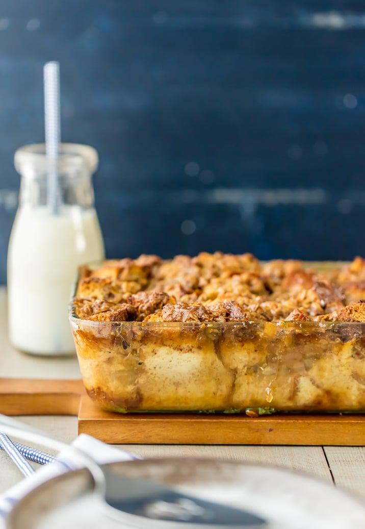 Plato para hornear lleno de pudín de pan de manzana con caramelo, con un tarro de leche en el fondo