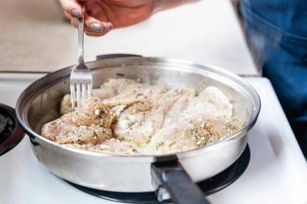 Pollo Congelador Comida con Pollo Tenders-tenedor volteando las ofertas de pollo en una sartén