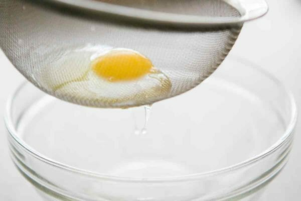 escurrir las claras de huevo a través del tamiz de malla fina