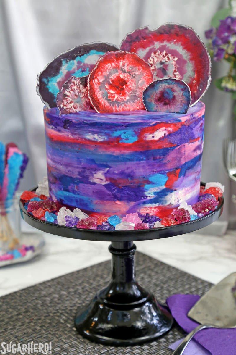 Pastel de ágata: pastel de acuarela púrpura, azul y rosa con rodajas de ágata comestibles en la parte superior   De SugarHero.com