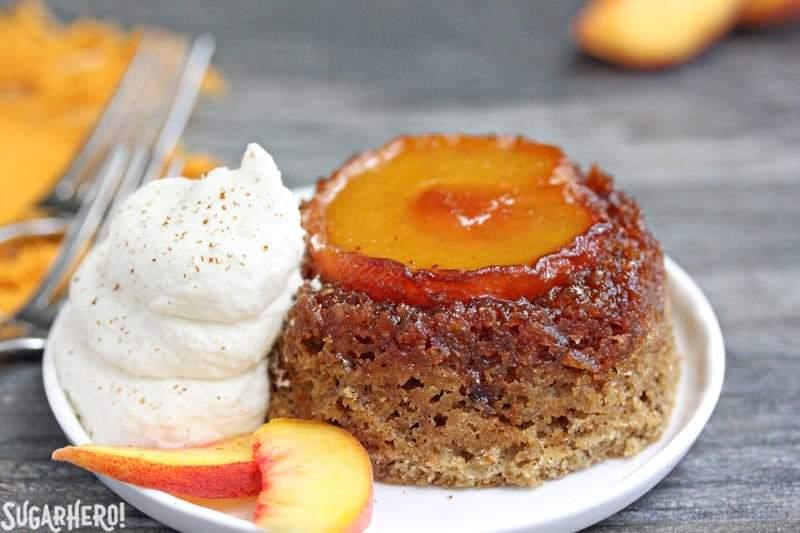 Primer plano de pasteles de durazno al revés en un plato con crema batida y rodajas de durazno fresco | De SugarHero.com