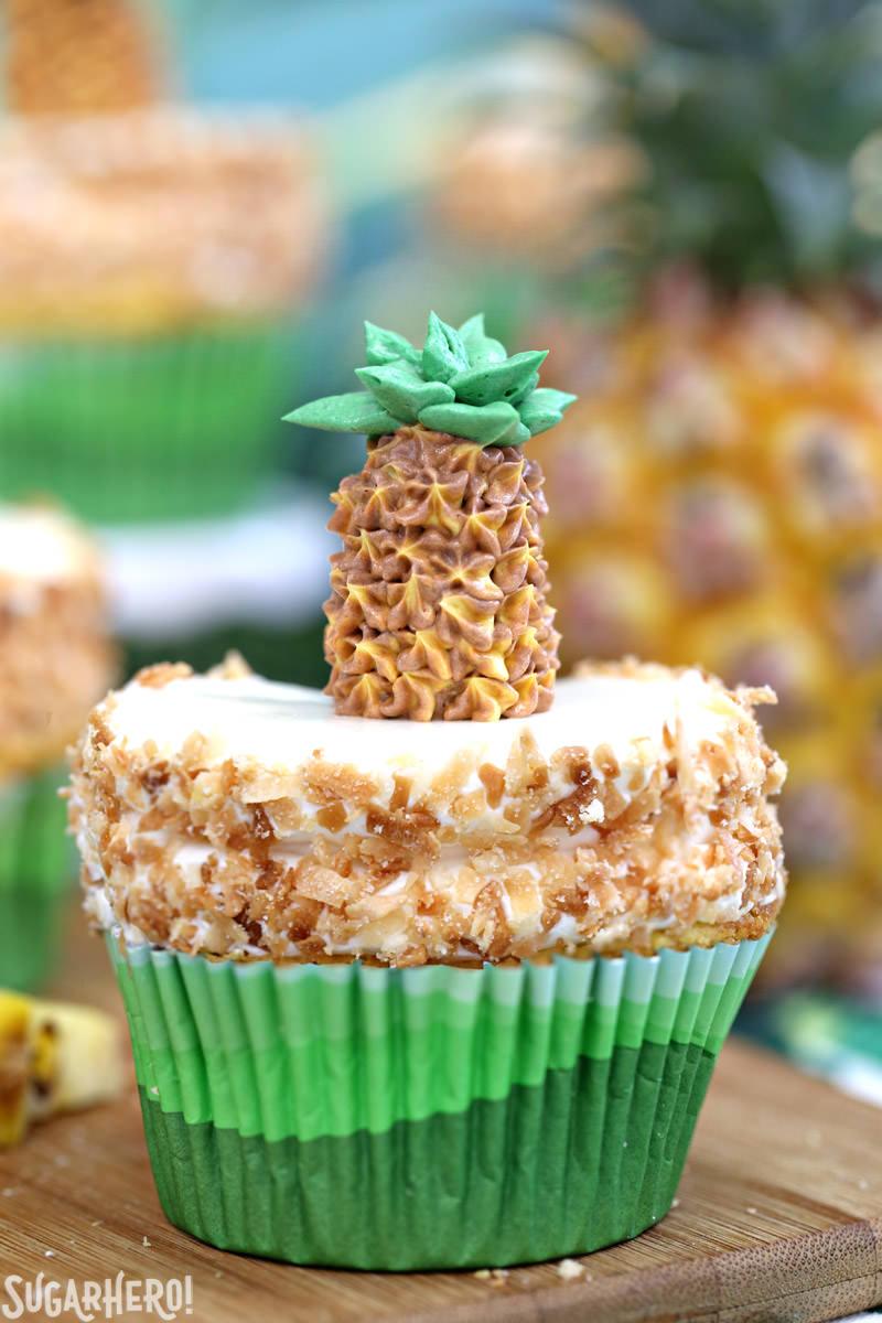 Primer plano de un pastelito de piña con glaseado de coco y una piña de crema de mantequilla en la parte superior | De SugarHero.com