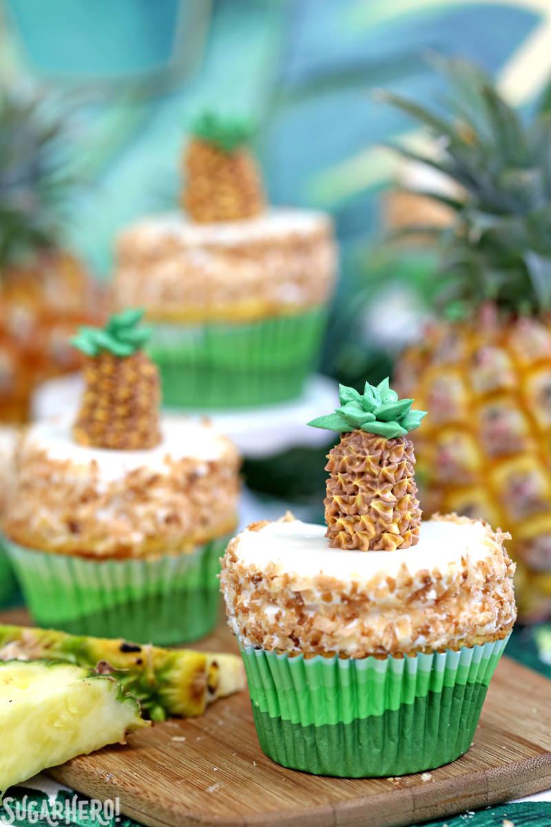 Grupo de tres pastelitos de piña con piña fresca en el fondo | De SugarHero.com