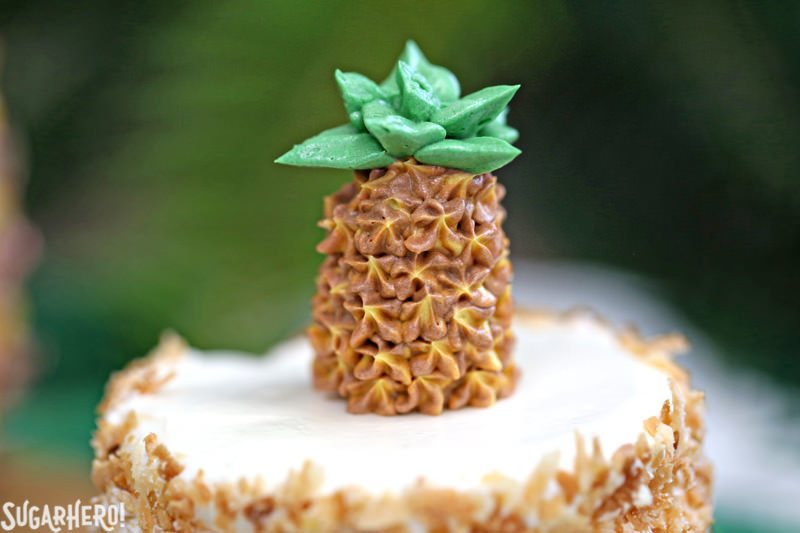 Primer plano de piña crema de mantequilla en la parte superior de los pastelitos de piña | De SugarHero.com