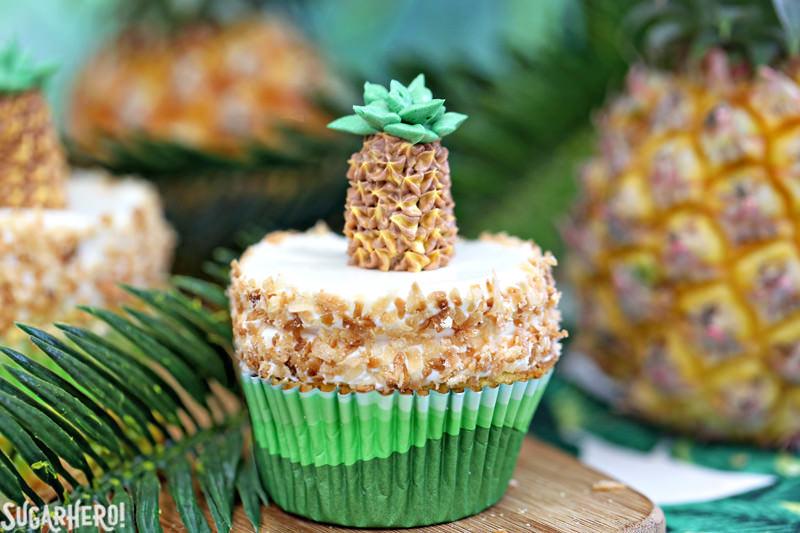 Magdalenas de piña: magdalenas de piña divertidas y tropicales con glaseado de coco. Además de una adorable piña de crema de mantequilla en la parte superior. El | De SugarHero.com