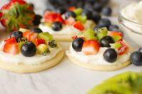 ¡Las galletas de pizza de frutas son toda la bondad que obtienes en una pizza de frutas individualizada! Corteza suave, glaseado de crema batida de vainilla, cubierto con sus frutas favoritas; fresas, frambuesas, arándanos, kiwi, moras, mango ... ¡las posibilidades son infinitas!
