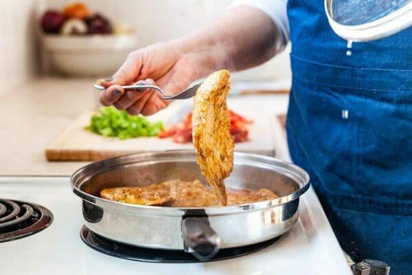 Easy Skillet Chicken: la mujer usa un tenedor para recoger la pechuga de pollo y darle la vuelta en una sartén