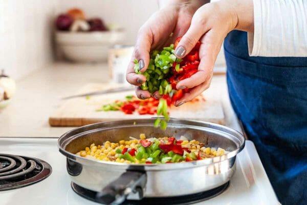 Receta de pollo en sartén con pimentón ahumado - manos de mujer agregando vegetales picados a la sartén con pollo