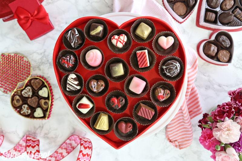 Caja de pastel de chocolates: imagen de arriba de pastel cubierto con chocolates caseros, con más chocolates repartidos por todas partes | De SugarHero.com