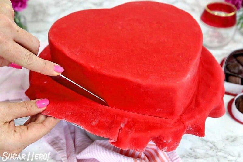 Caja de pastel de bombones: cortar el exceso de fondant rojo de la base del pastel | De SugarHero.com