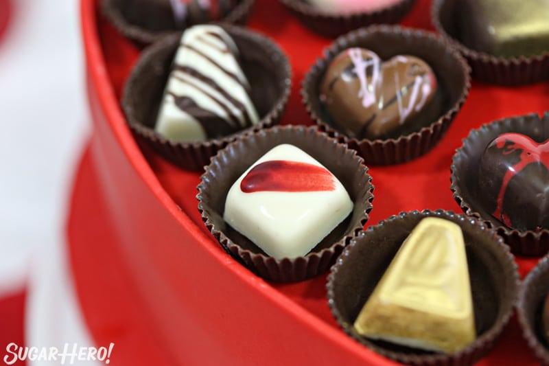 Caja de pastel de bombones - primer plano de bombones caseros encima del pastel | De SugarHero.com