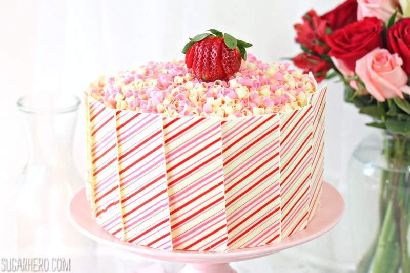 Pastel de capas de fresas y crema: pastel con paneles de chocolate blanco a rayas rosas y blancas y rizos de chocolate blanco y rosa en la parte superior | De SugarHero.com