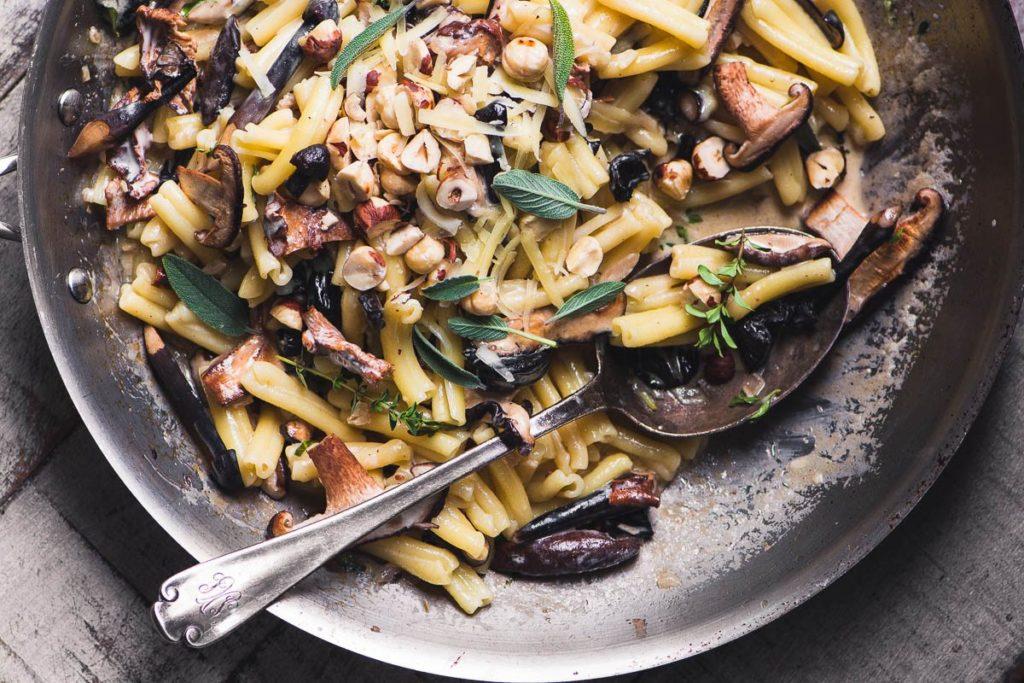 Pasta con champiñones y avellanas en una sartén con una cuchara grande