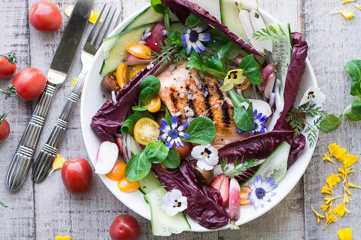 Toma cenital de ensalada de salmón a la parrilla con flores comestibles