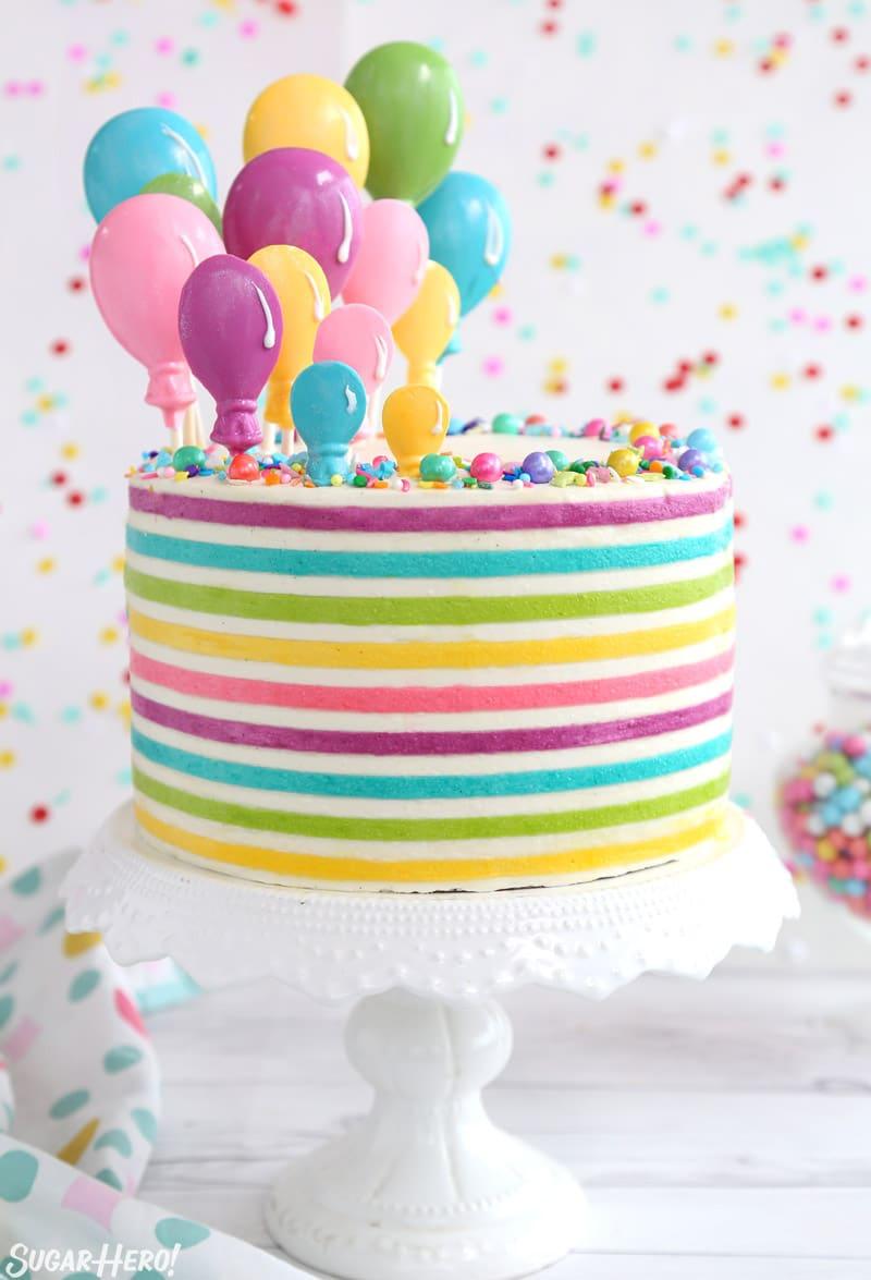 Pastel de globo de crema de mantequilla a rayas: un pastel redondo con brillantes y coloridas rayas de crema de mantequilla y globos de caramelo que se elevan desde la parte superior | De SugarHero.com