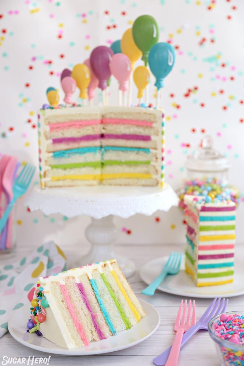Pastel de globo de crema de mantequilla a rayas: pastel cortado con varias rebanadas dispuestas delante de él | De SugarHero.com