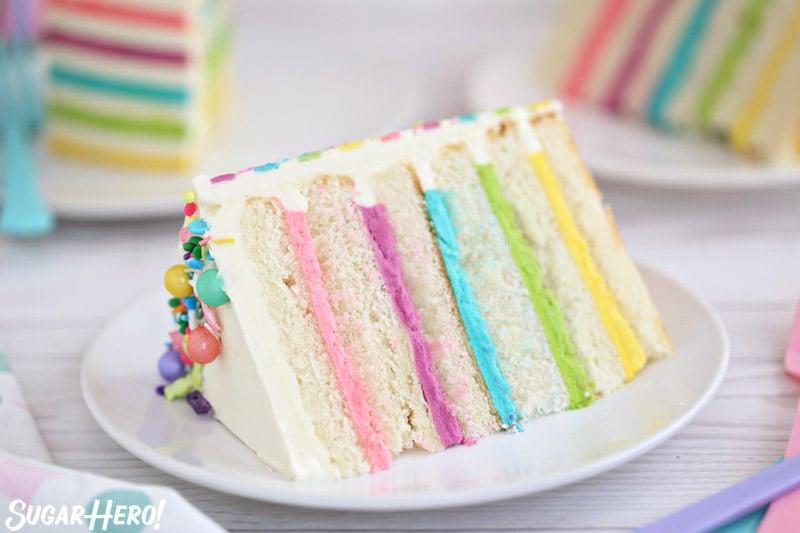 Pastel de globo de crema de mantequilla a rayas: foto de primer plano de una sola rebanada de pastel, con varias rebanadas en el fondo | De SugarHero.com