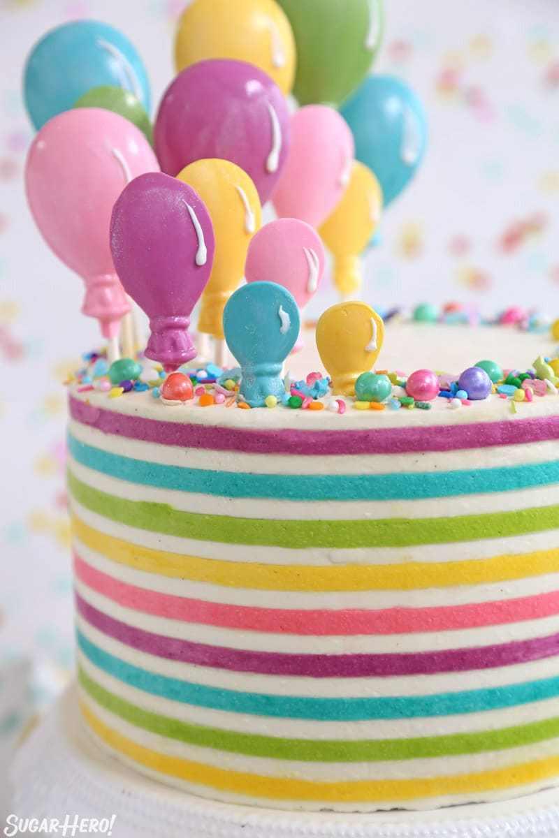 Pastel de globo de crema de mantequilla a rayas: imagen vertical en primer plano de coloridas rayas de crema de mantequilla y globos de caramelo en la parte superior del pastel | De SugarHero.com