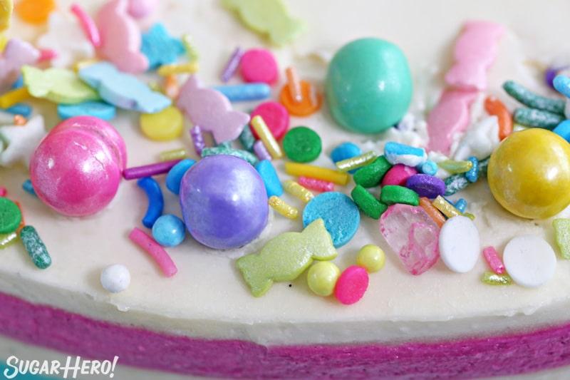 Pastel de globo de crema de mantequilla a rayas - primer plano del surtido de espolvorear encima del pastel | De SugarHero.com