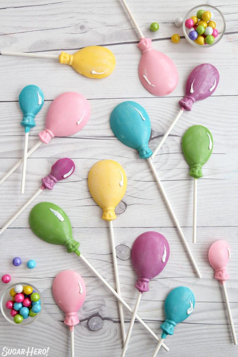 Pastel de globo de crema de mantequilla a rayas piruletas de globos de caramelo dispuestas sobre un fondo blanco de madera | De SugarHero.com