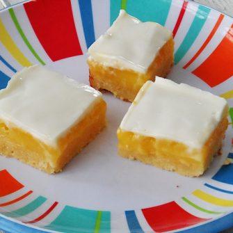 Barras de limón con cobertura de crema agria dulce a través de AmandasCookin.com @ amandaformaro