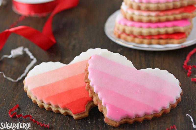 Brown Butter Heart Cookies: dos galletas de azúcar, una ombre roja y una rosa ombre, con una pila de galletas detrás | De SugarHero.com