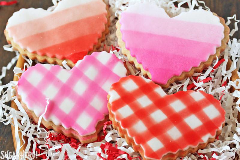 Brown Butter Heart Cookies: dos galletas a cuadros y dos galletas ombre en un tazón de madera | De SugarHero.com
