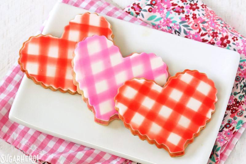 Brown Butter Heart Cookies: tres galletas con un patrón de cuadros en un plato blanco | De SugarHero.com