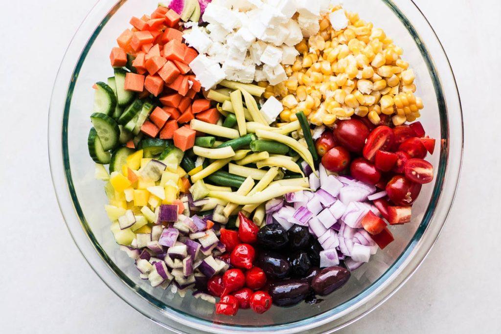 Ingredientes picados para granjeros comercializan ensalada de verduras en un recipiente de vidrio