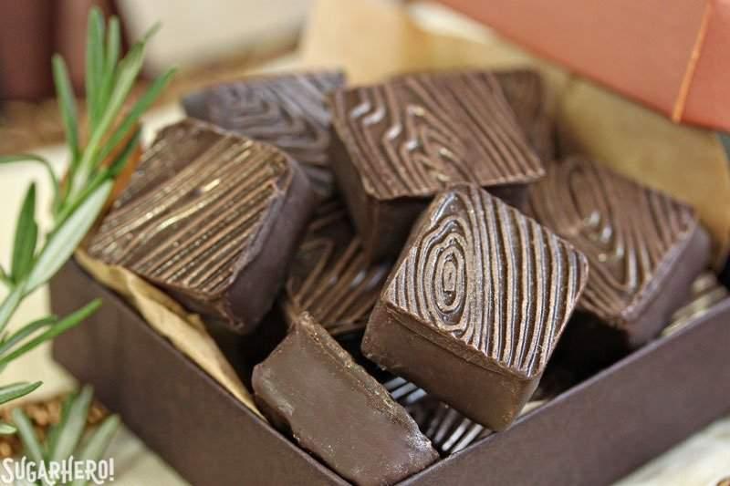 Trufas de frambuesa y romero: primer plano de trufas de frambuesa y romero cuadradas con un patrón de grano de madera con manchas de oro | De SugarHero.com