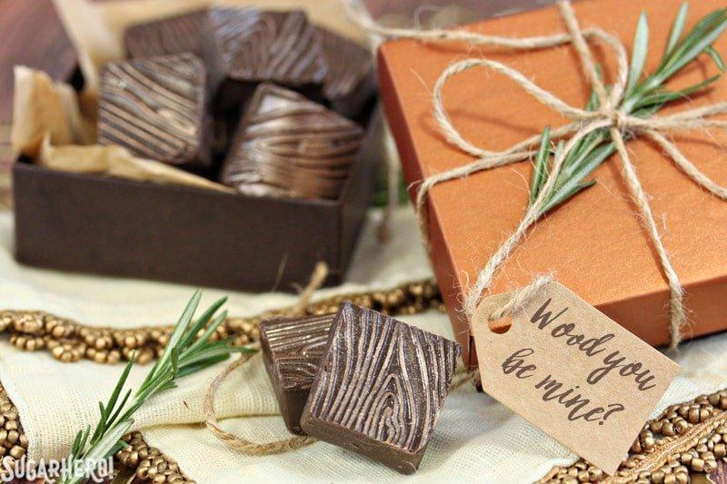 Trufas de frambuesa y romero: trufas de chocolate cuadradas con un patrón de grano de madera, en una caja de dulces decorativa con un