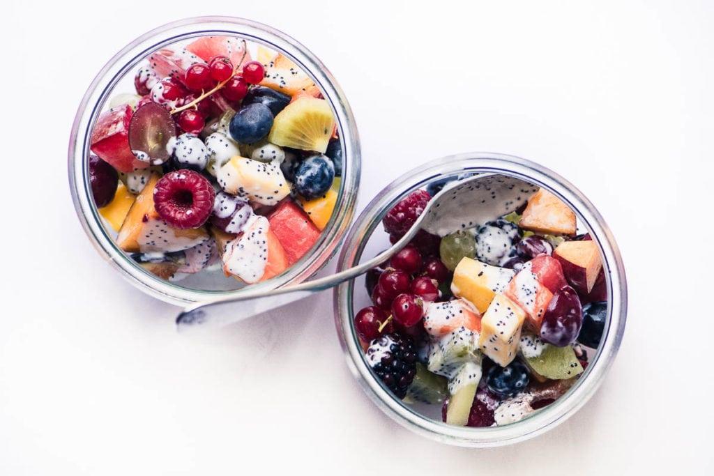 Ensalada de frutas de verano con aderezo de semillas de amapola kéfir en dos tazones de vidrio