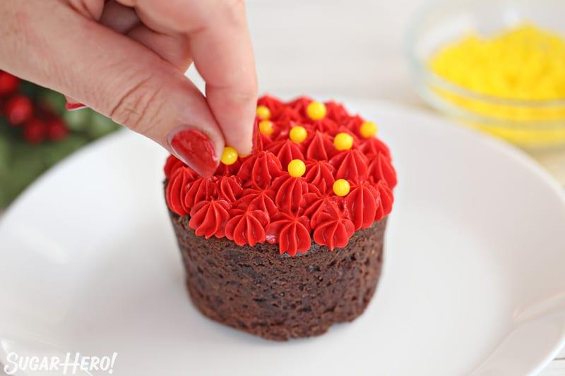 Flores de chocolate en flor: decorar las copas de las tazas de brownie de menta con estrellas de glaseado rojo y perlas de azúcar amarillas | De SugarHero.com