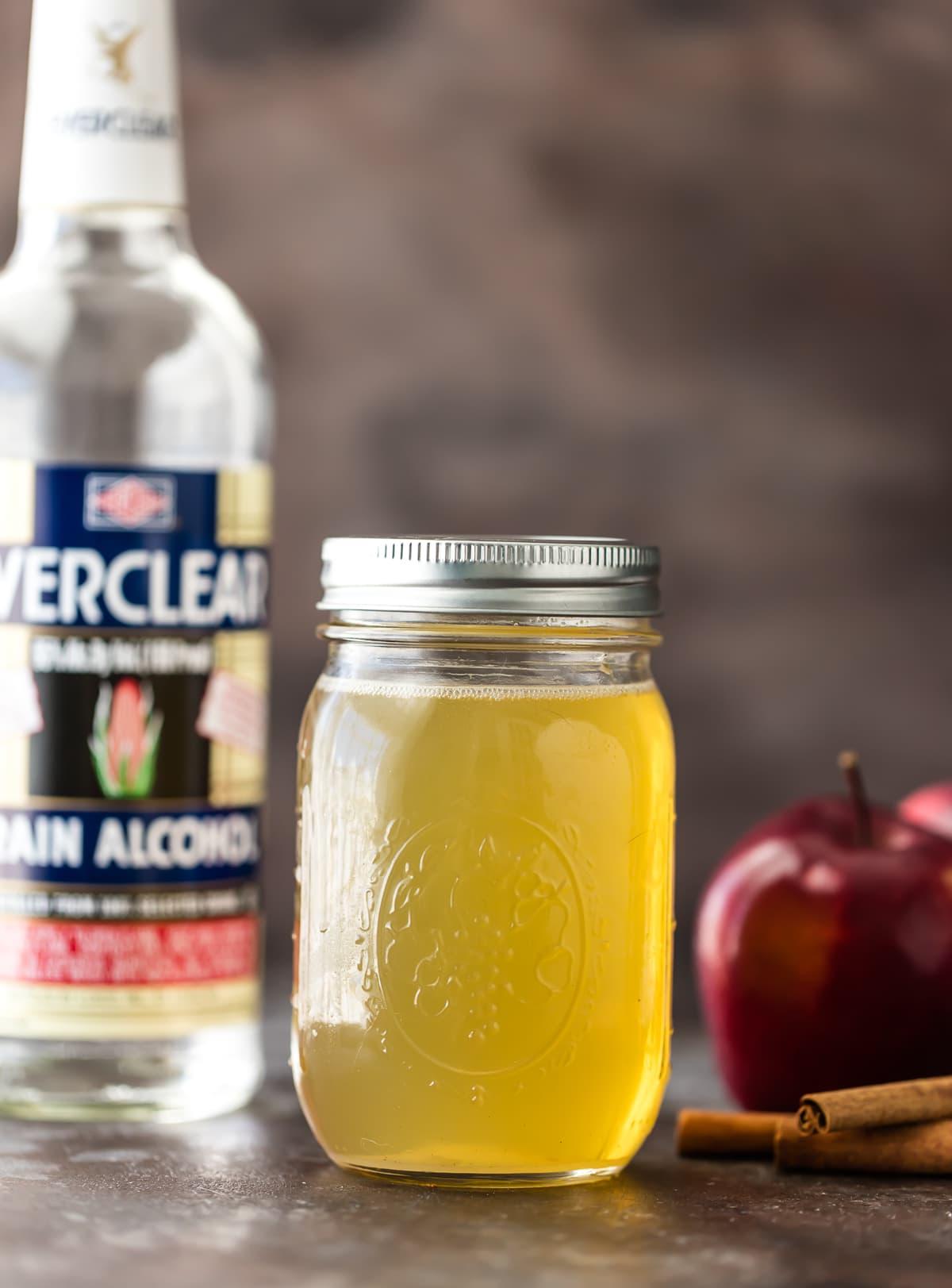 Un frasco de vodka casero de manzana junto a una botella de everclear